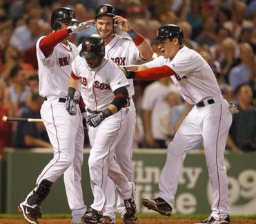 Dustin Pedroia, center, is welcomed home by Jarrod Saltalamacchia, Jacoby Ellsbury and Adrian Gonzalez after a three-run home run in the sixth inning.